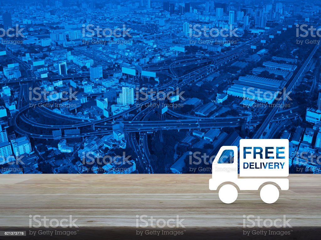 Free delivery truck icon on wooden table over city stock photo