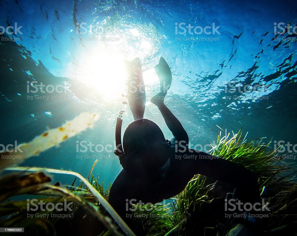 Free diver spearfishing in the abyss stock photo