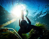 Free diver spearfishing in the abyss