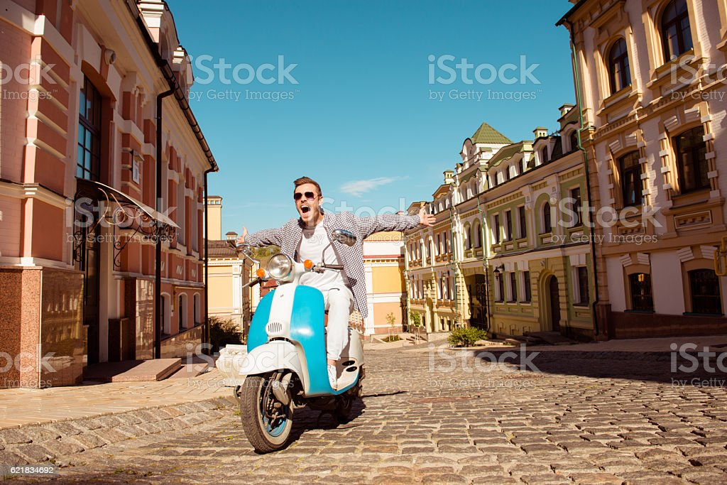 free happy man riding scooter with open hands stock photo