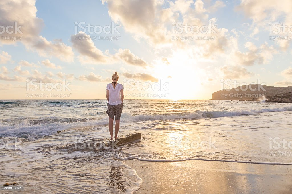 Free Happy Woman Enjoying Sunset on Sandy Beach stock photo