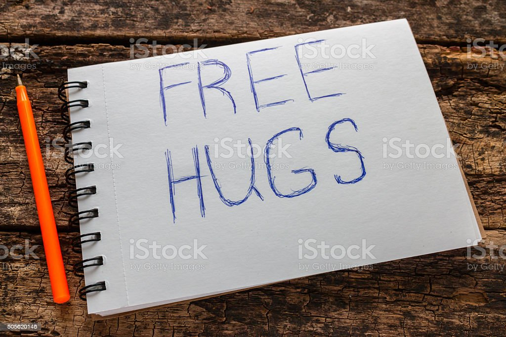 free hugs sign on the notebook and pen stock photo