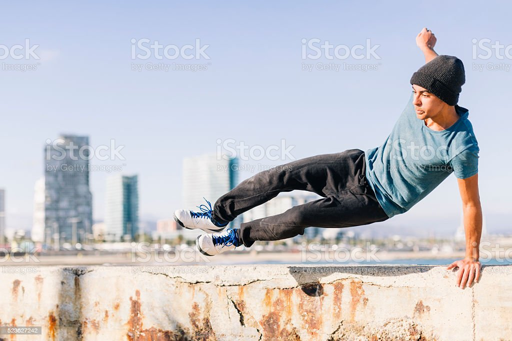 Free running athlete in the streets and beach of Barcelona. Parkour