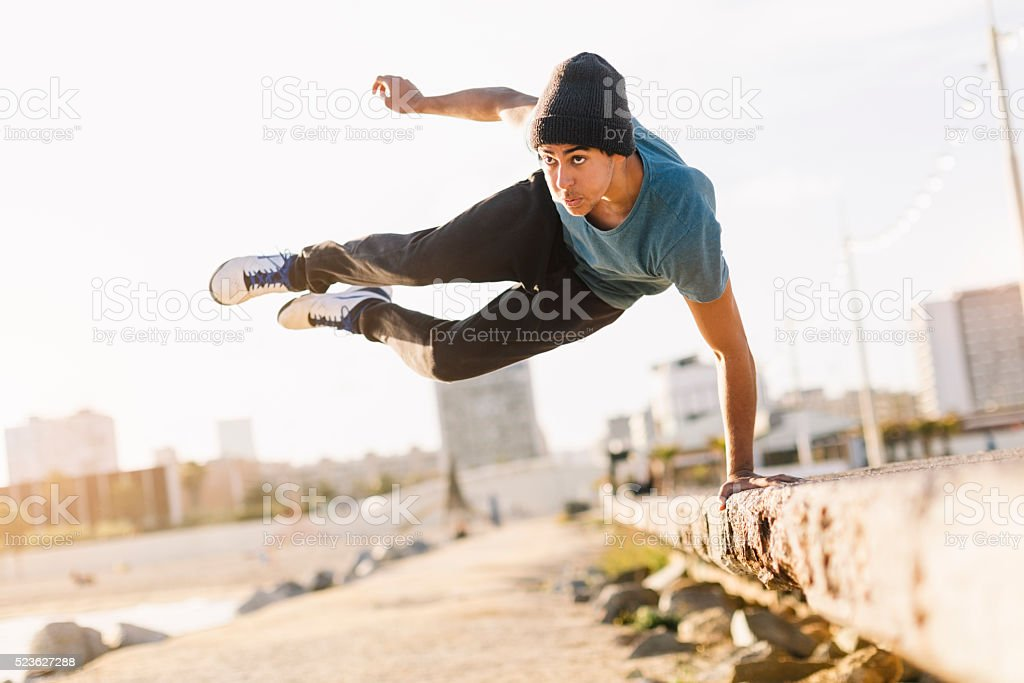 Free running parkour athlete in the beach of Barcelona stock photo