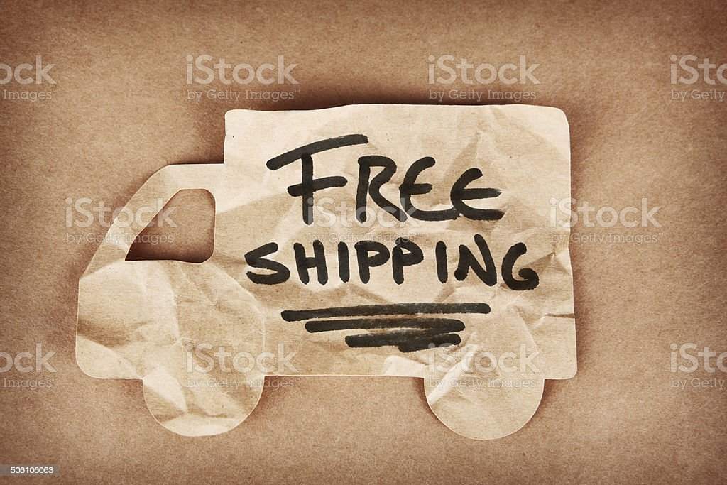 Free Shipping Written on Crumpled Cardboard Cutout Truck stock photo