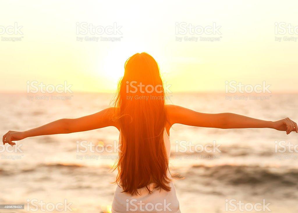Free woman enjoying freedom feeling happy at beach at sunset. stock photo