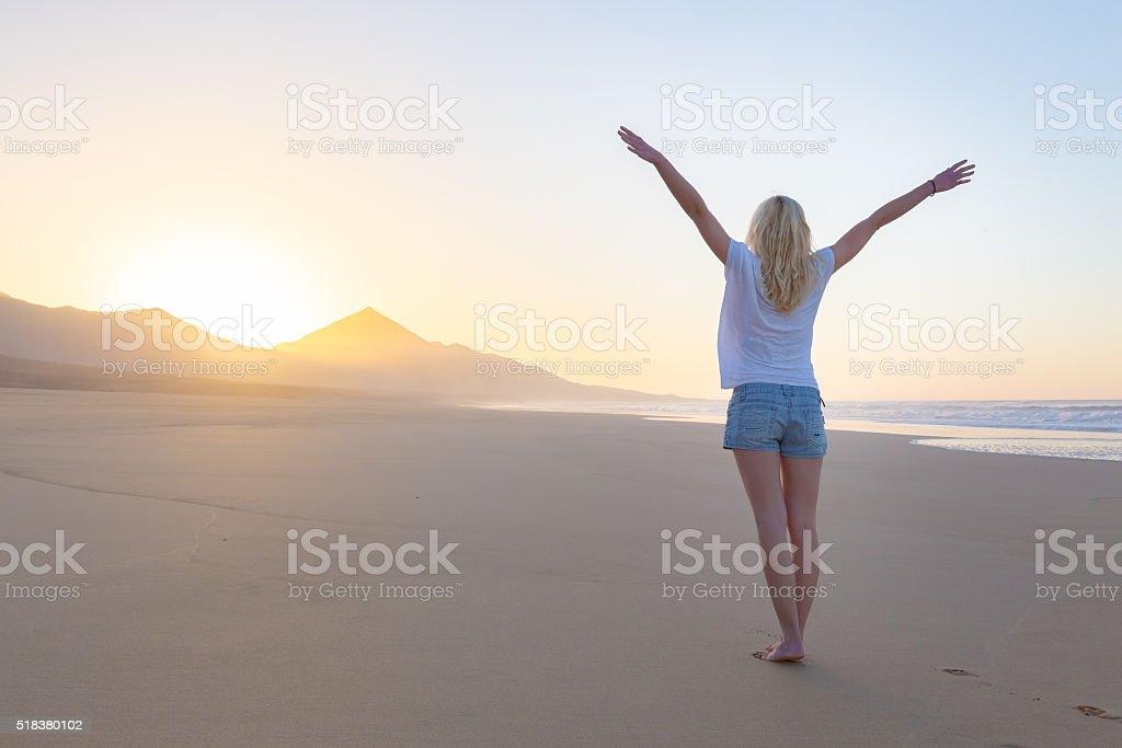 Free woman enjoying freedom on beach at sunrise. stock photo
