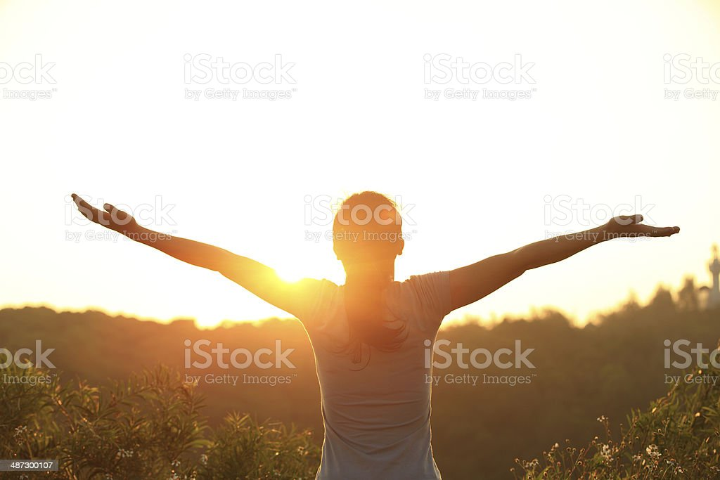 free woman open arms to sunrise stock photo