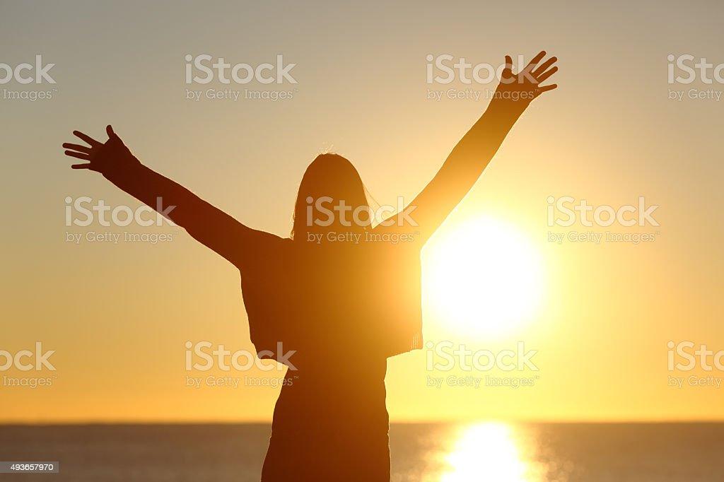 Free woman raising arms watching sun at sunrise stock photo