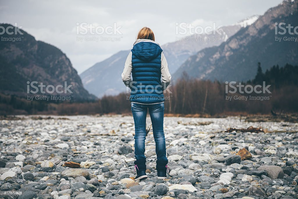 Freedom. Unrecognizable female person looking on mountains. stock photo
