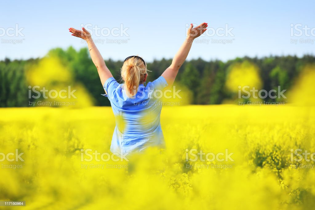 Freedom - Woman with raised Arms in a Colza Field stock photo