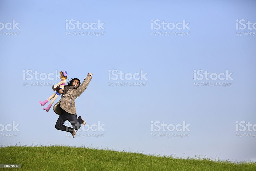 Freedom Young Girl jumping over the field with outstretched hands. royalty-free stock photo