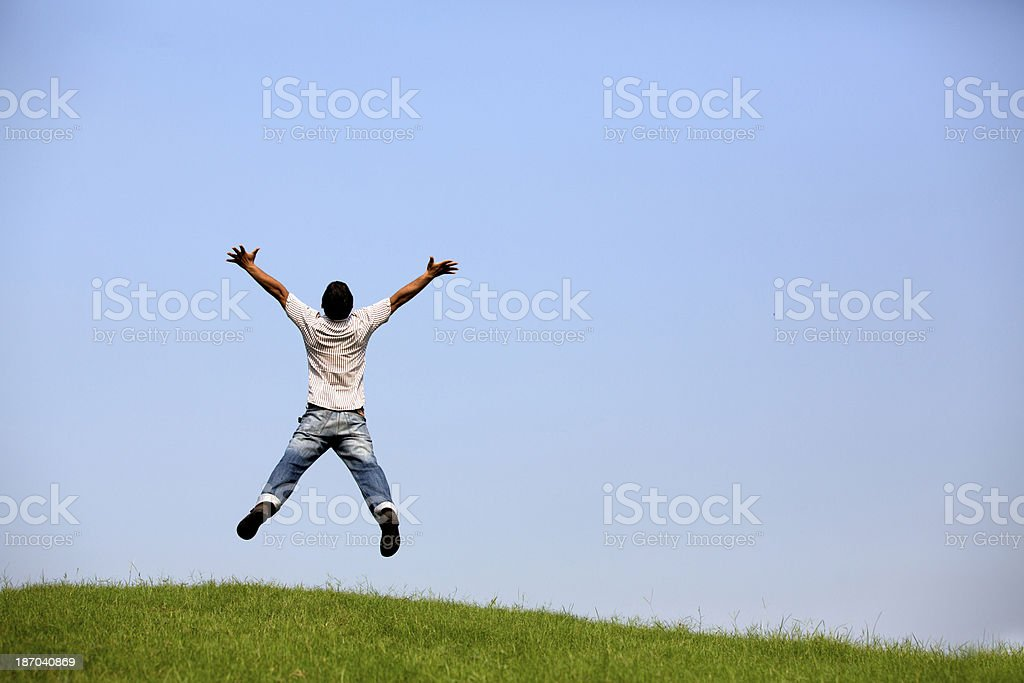 Freedom Young man jumping over the field with outstretched hands. royalty-free stock photo