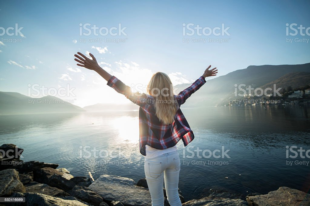 Freedom-Woman arms outstretched by the lake stock photo