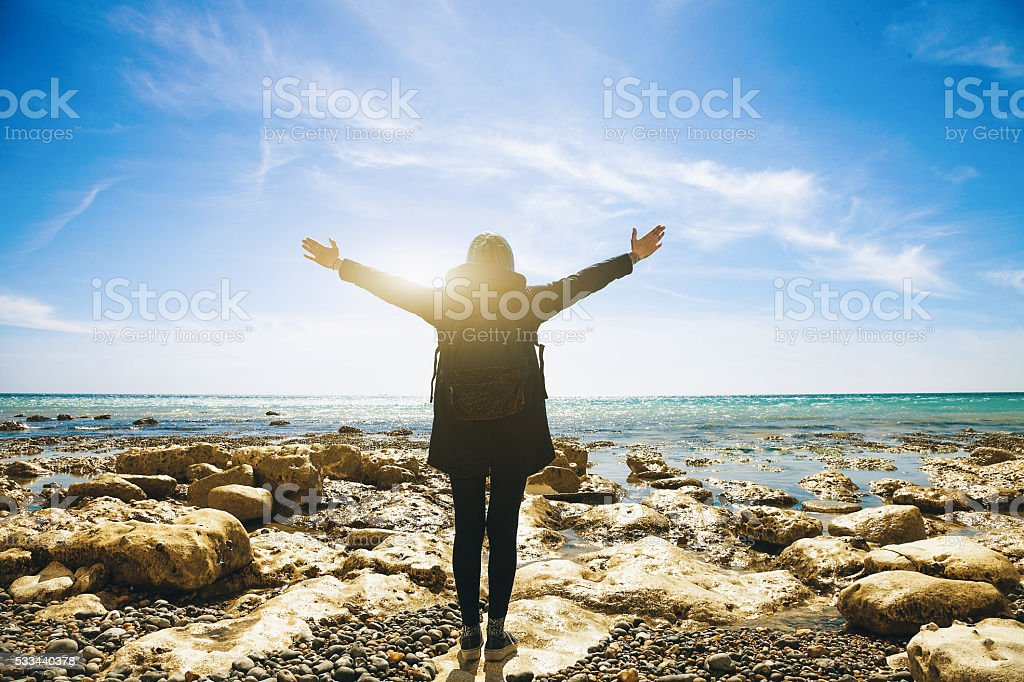 Freedom-Woman arms outstretched by the sea stock photo