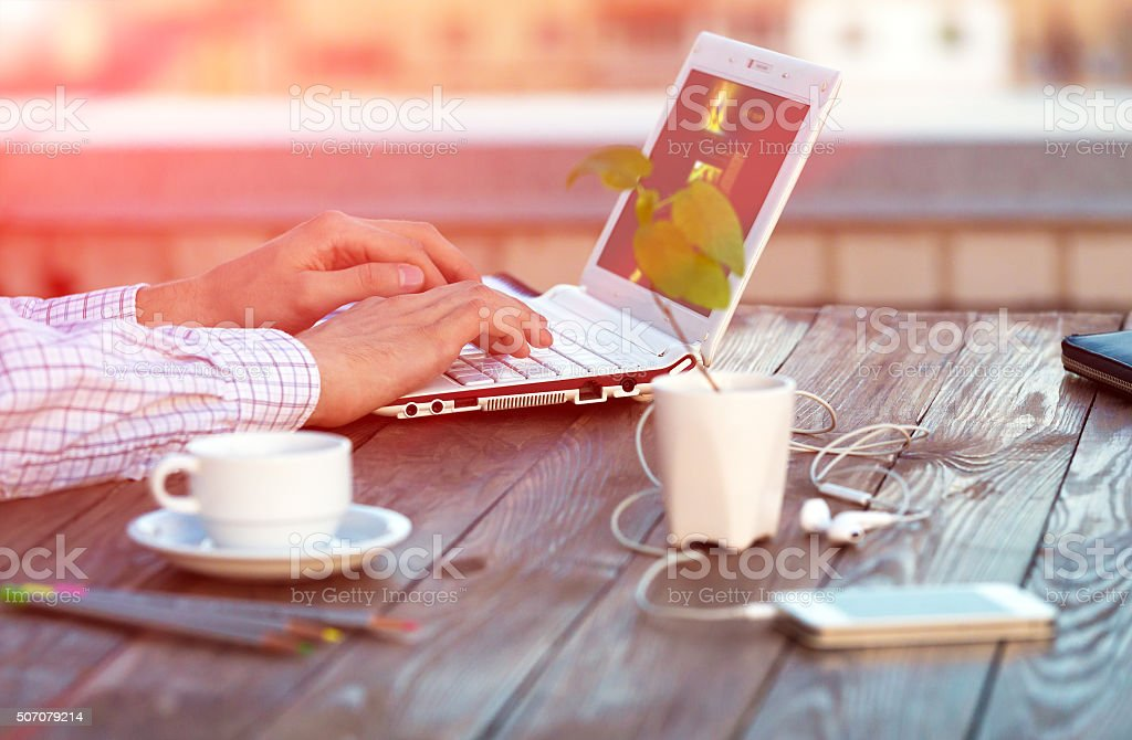 Freelance work at wood Table located on outdoor terrace stock photo