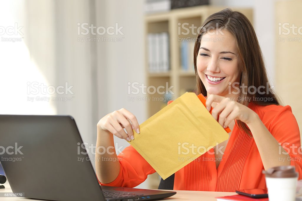 Freelancer opening a padded envelope stock photo