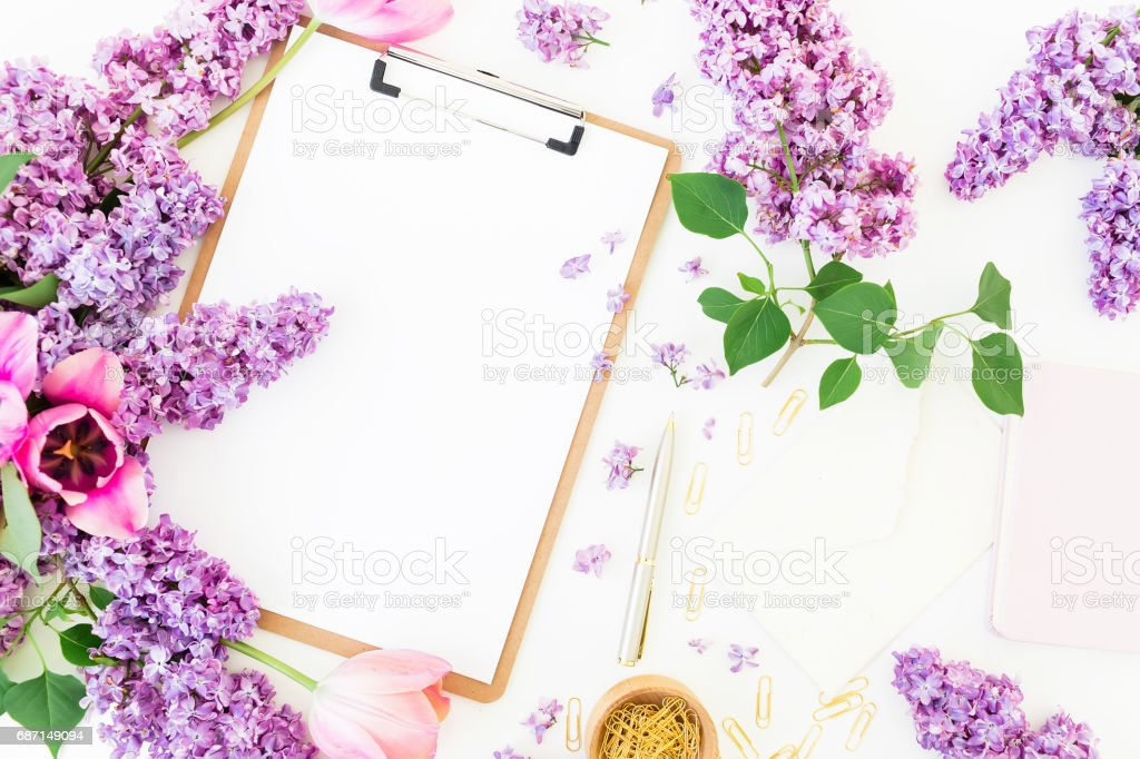 Freelancer or blogger workspace with clipboard, notebook, envelope, lilac, and tulips on white background. Flat lay, top view. stock photo