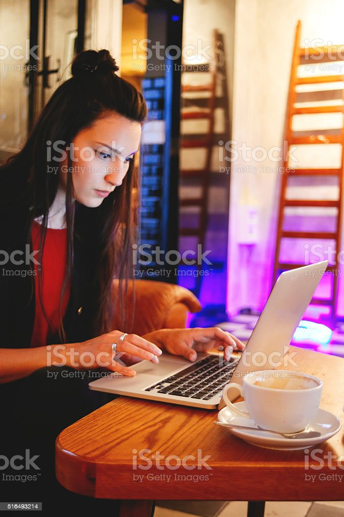 Freelancer woman designer with a laptop in a cafe stock photo
