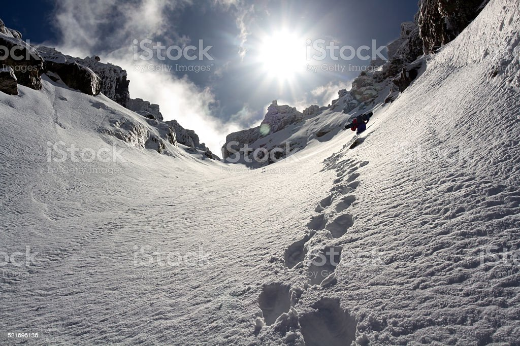 Free-rider climbing a steep cliff after heavy snowfall stock photo