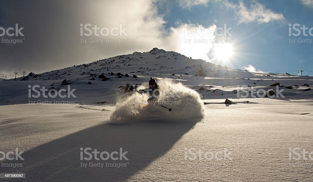 Free-riding skier making a turn in the fresh powder snow stock photo