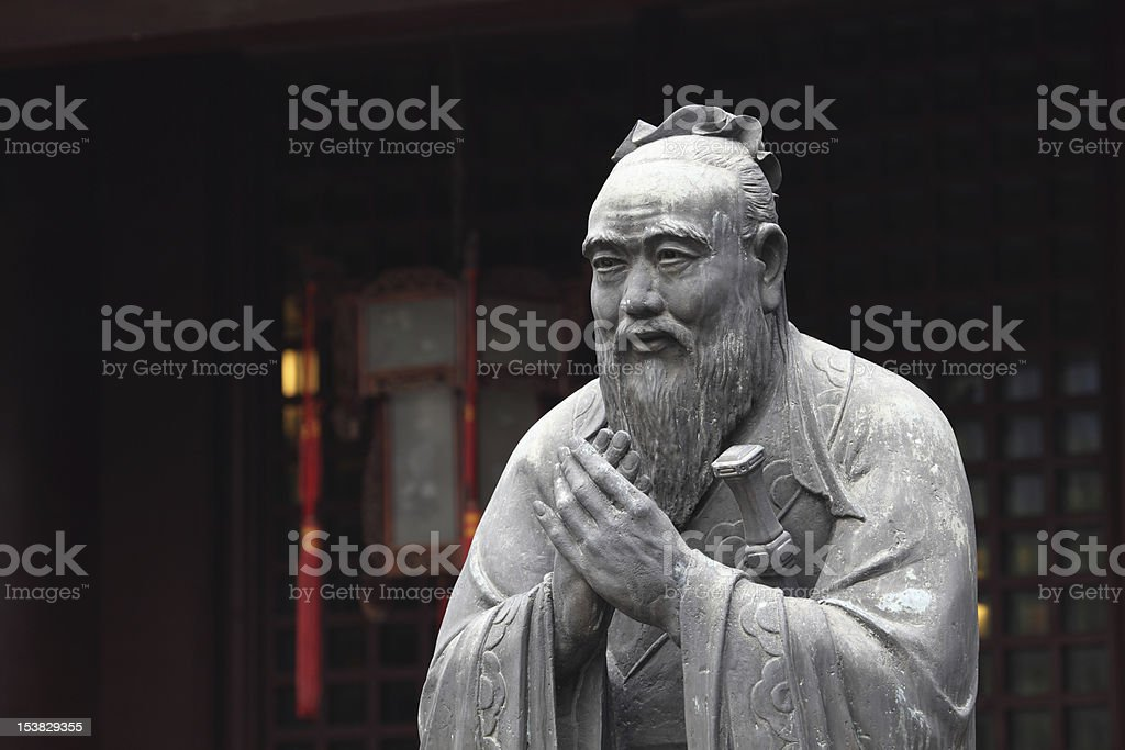 Freestanding, grey stone statue of Confucius outside temple stock photo