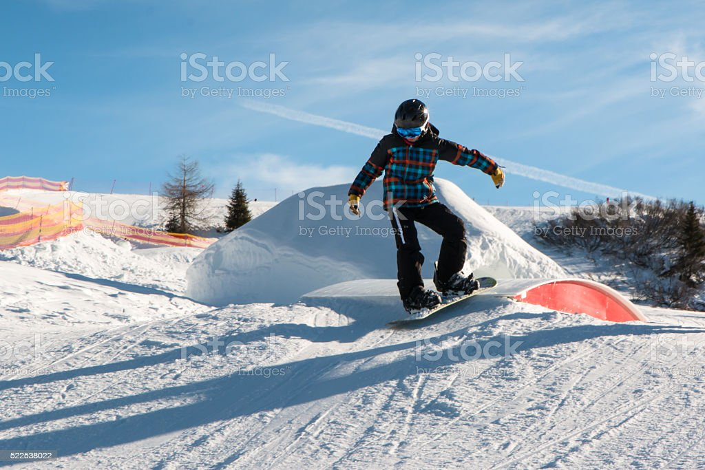 freestyle snowboarder with helmet in snowpark stock photo