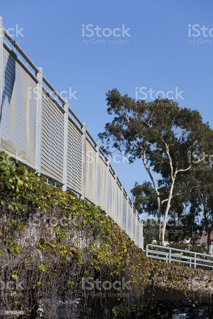Freeway overpass sidewalk with railing and ivy royalty-free stock photo
