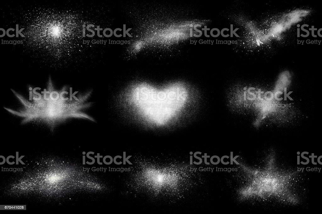 Freeze motion of 9 white powder shapes, isolated on black, stock photo
