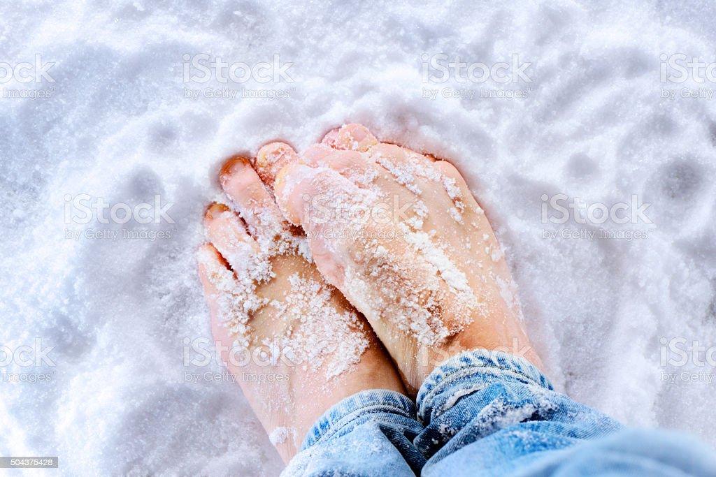 Freezing bare feet on ice stock photo