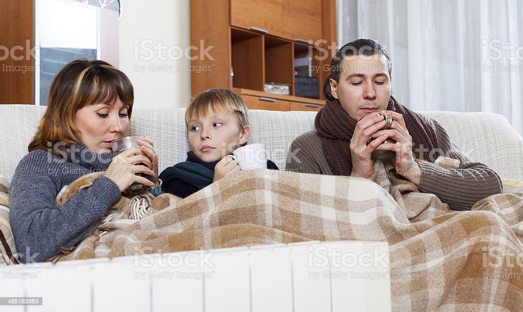 freezing family of three   warming near warm radiator stock photo
