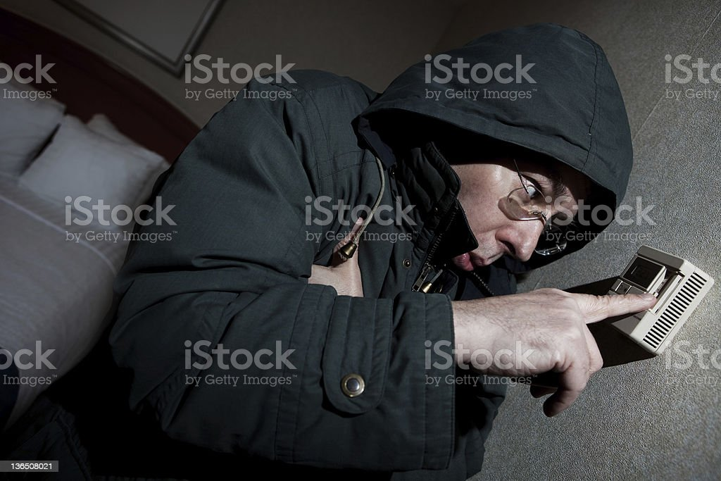 Freezing man adjusting thermostat stock photo