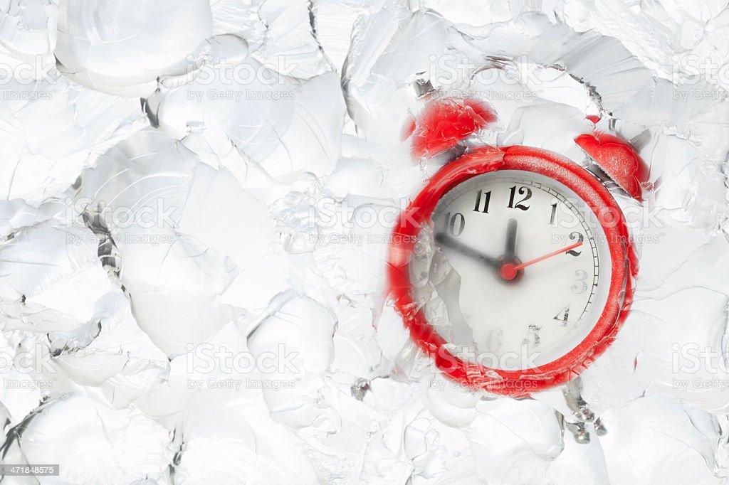 Freezing time alarm clock in block of ice stock photo