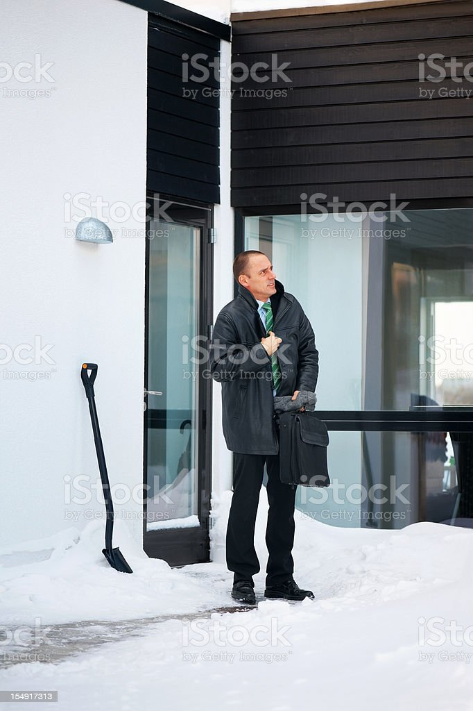 Freezing trendy man outside stylish home in the snow stock photo