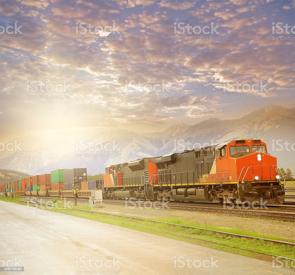 Freight train in Canadian rockies at sunset. stock photo