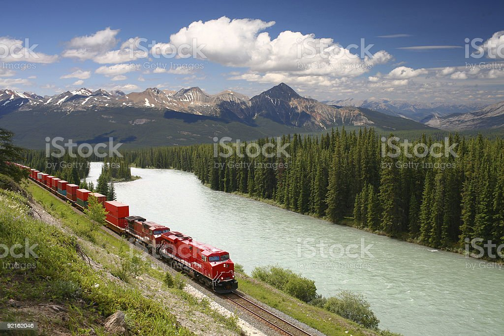 Freight train moving along river stock photo