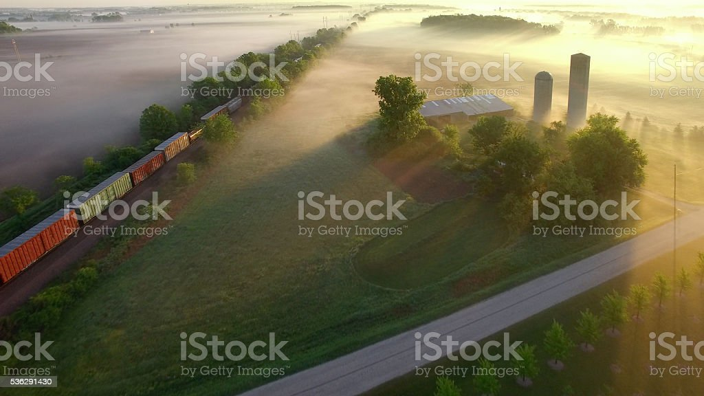 Freight train rolls across breathtaking, foggy landscape at sunrise stock photo