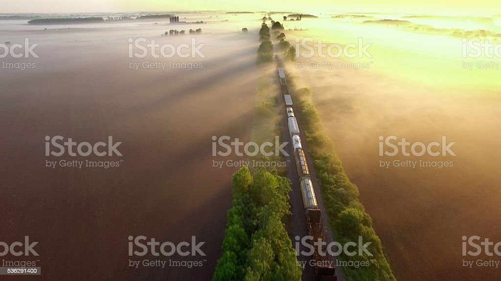 Freight train rolls across surreal, foggy landscape at sunrise stock photo
