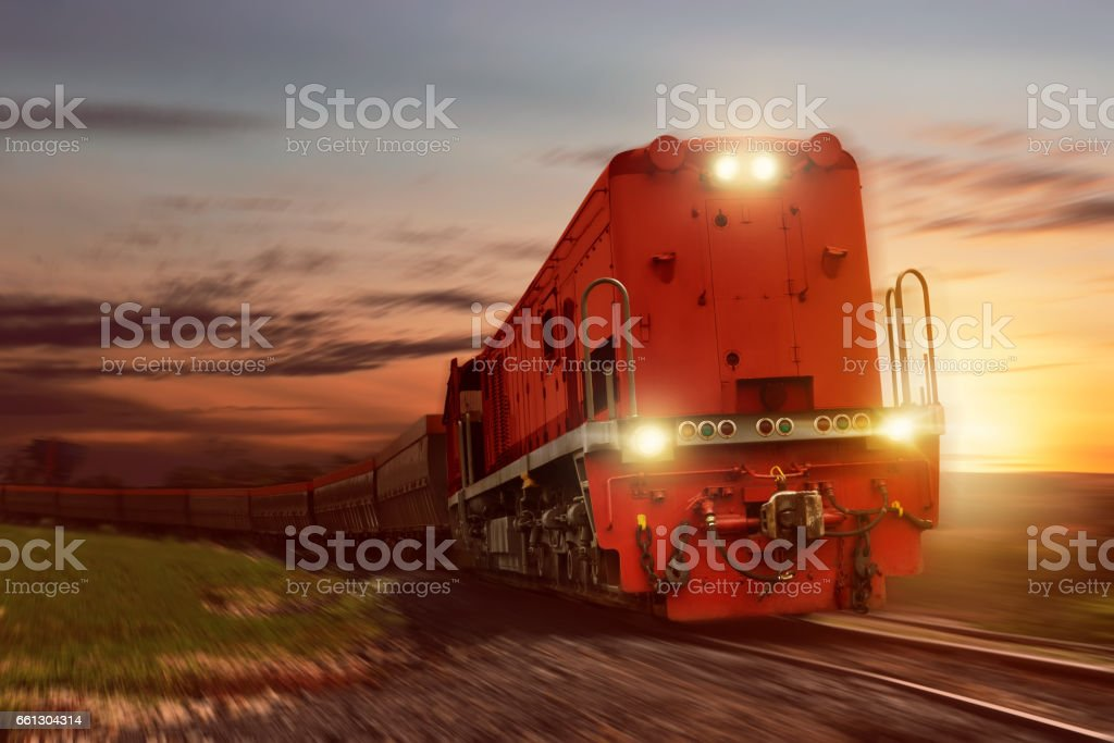 Freight train with cargo cars carrying coal at sunset
