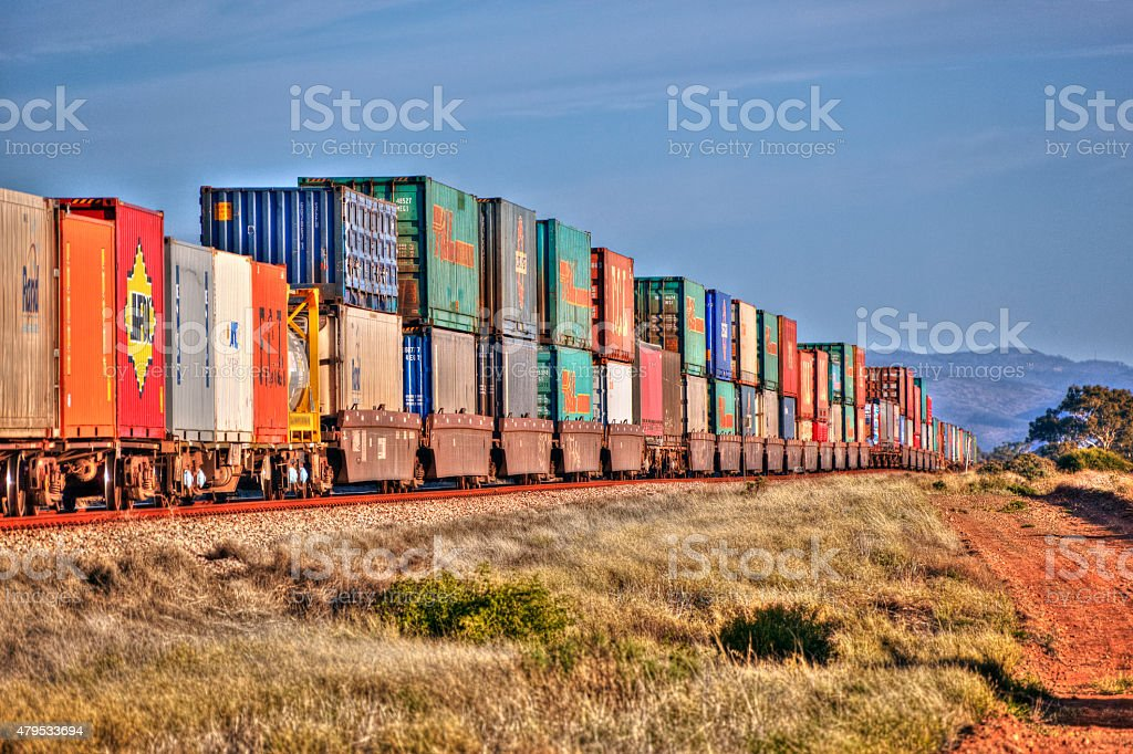 Freight train with multi-coloured stack containers on outback tracks stock photo