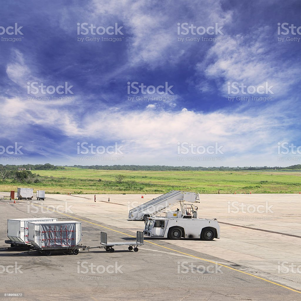 Freight trolleys with loaded baggage on the runway tarmac stock photo