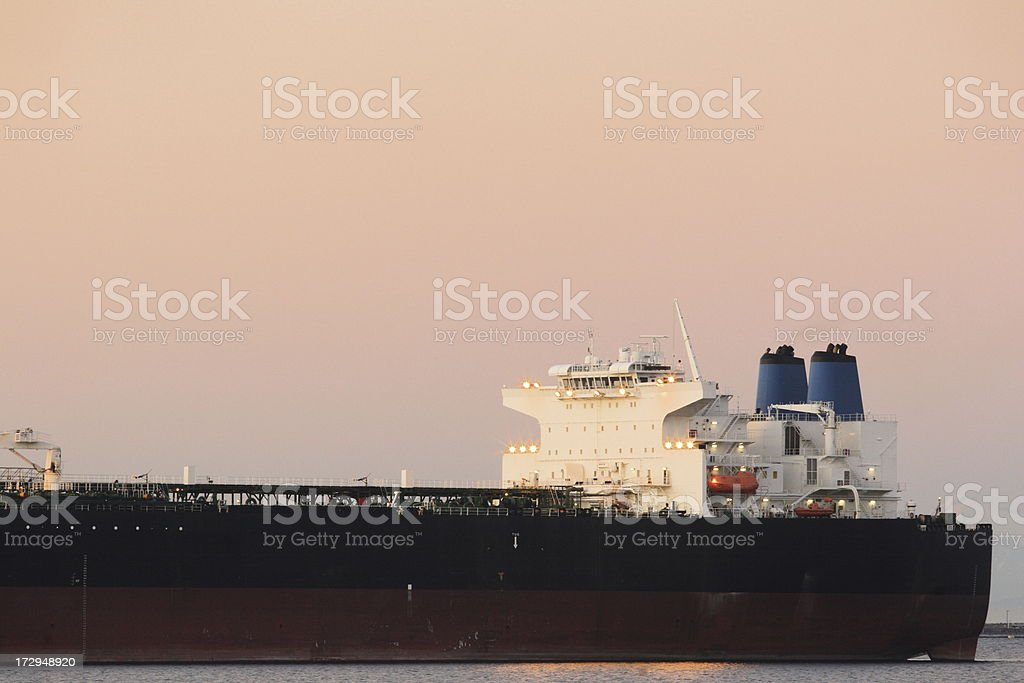 Freighter ship at ocean harbor mooring with pink sky sunset. Port...