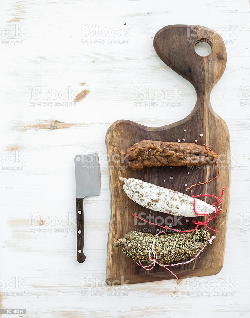 French alsacian smoked salamis on rustic walnut wooden chopping board stock photo