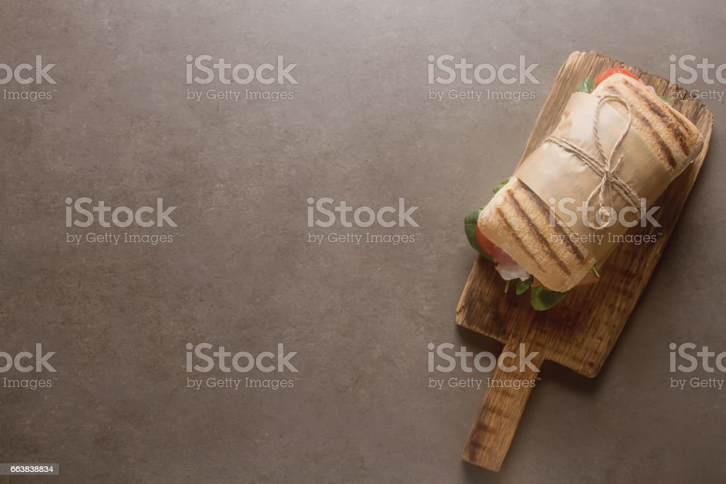 French baguette with sausage, tomatoes and lettuce. Dark background. stock photo