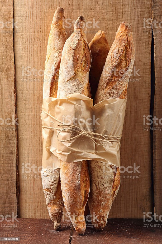 French baguettes in paper on wooden background stock photo