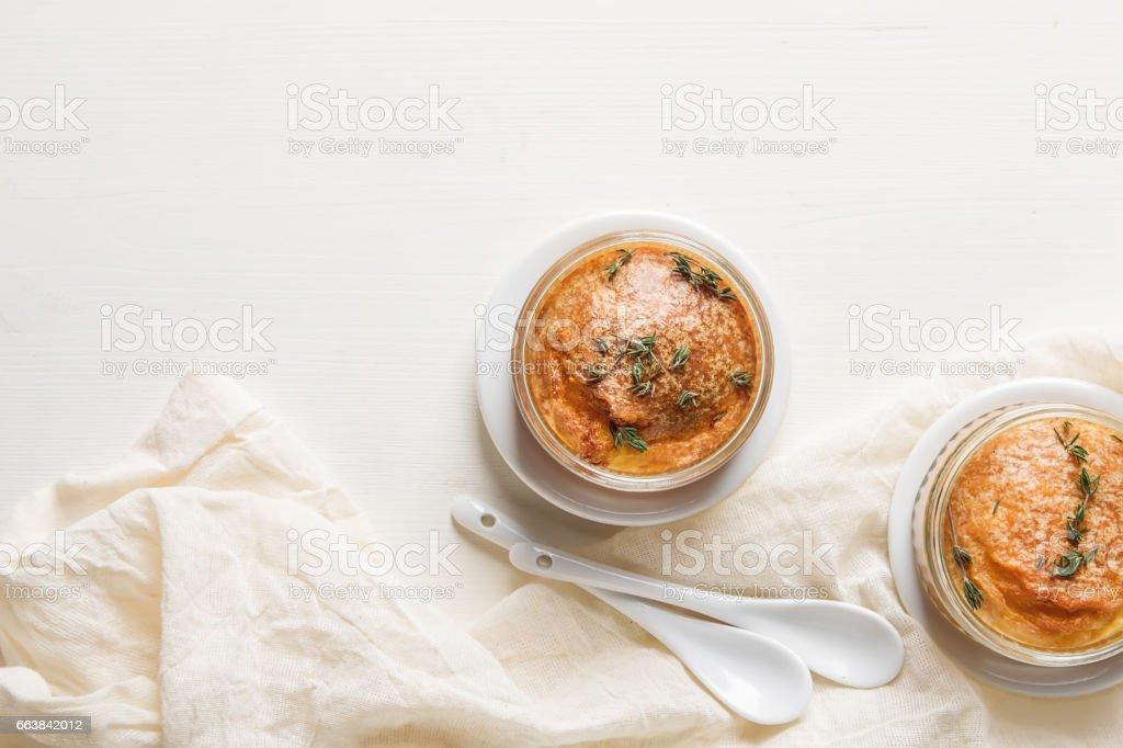French baked cheese souffle close-up on a table. Light white background. stock photo