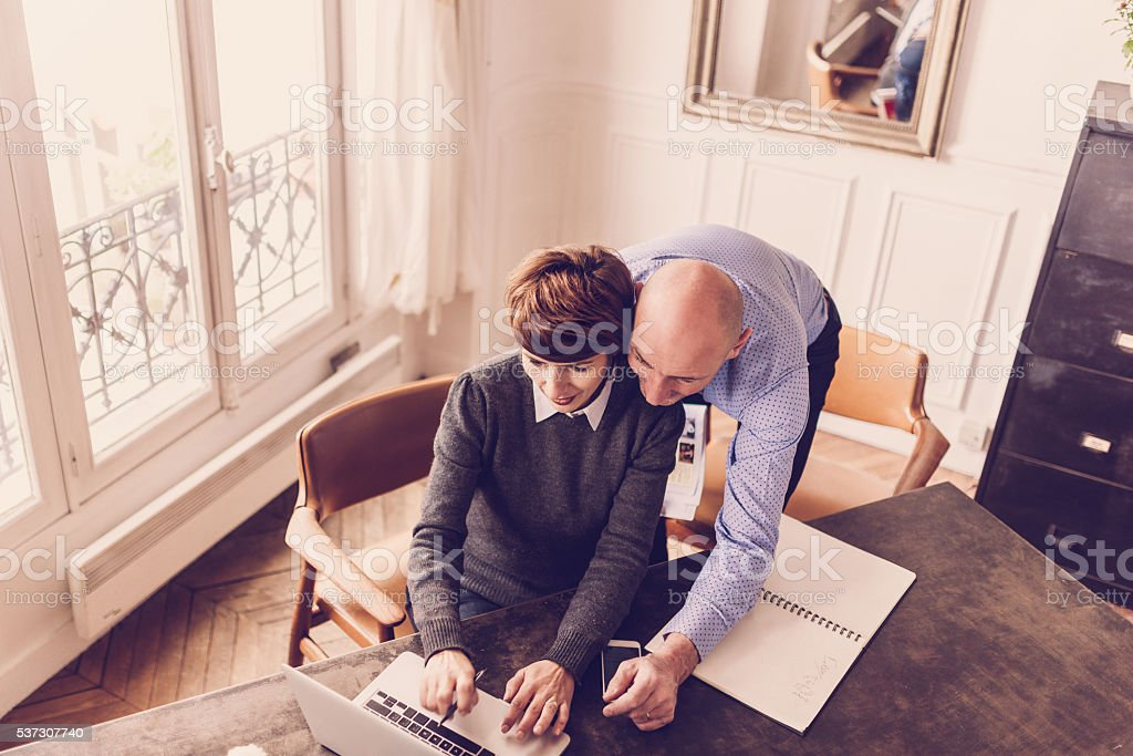 french couple looking together on laptop computer at home stock photo