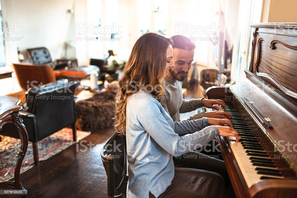 french couple playing the piano in a parisen house stock photo