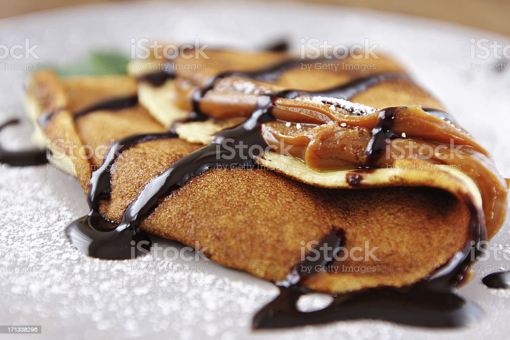 French crepes with caramel fudge on a spoon over stock photo