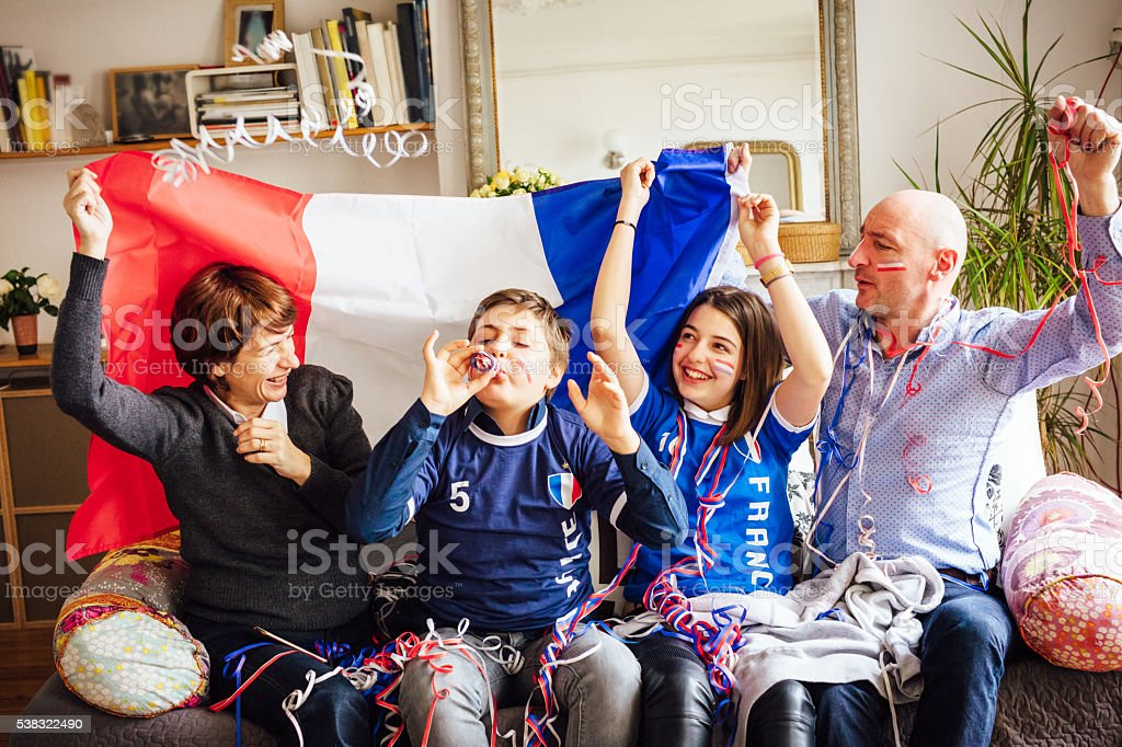 french family celebrating soccer event at home stock photo